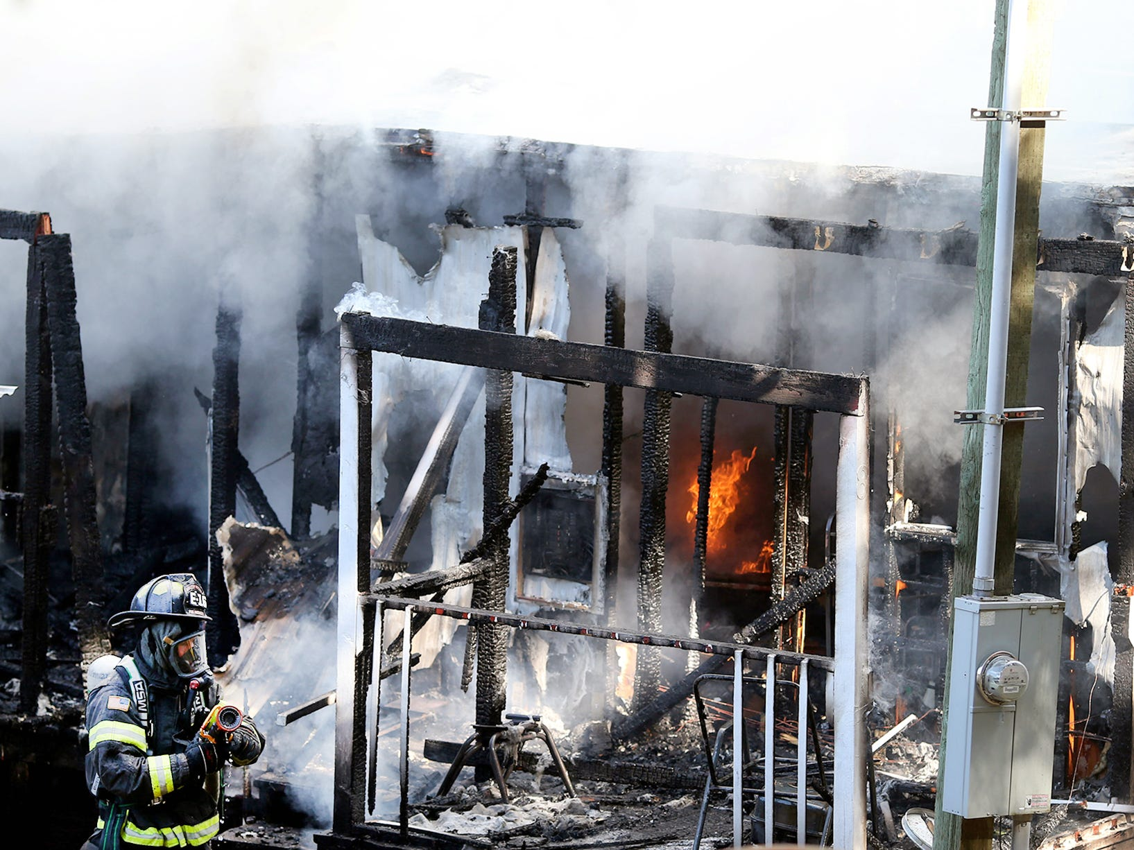 Firefighters work the scene of a mobile home fire at Rocky Point on Tuesday morning.