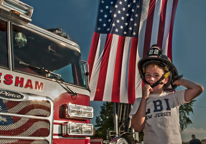 Jonathan Nawrocki, 9, of Marlton checks out firefighter equipment during a previous National Night Out in Evesham. A number of South Jersey communities plan events to celebrate this year's National Night Out on Aug. 7.