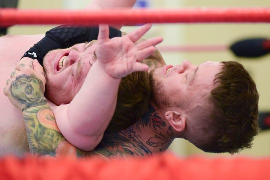 Eric Smalls goes for the pin against his opponent Little Bam Bam to win the match at a wrestling event held for veterans at the VA Medical Center on Saturday.