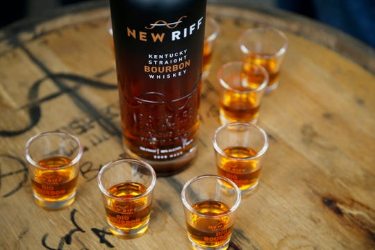 Shot glasses are filled before the toast during an attempt at the world's biggest bourbon toast hosted by New Riff Distillery on the Kentucky side of the Purple People Bridge in Newport, Ky., on Tuesday, July 31, 2018.