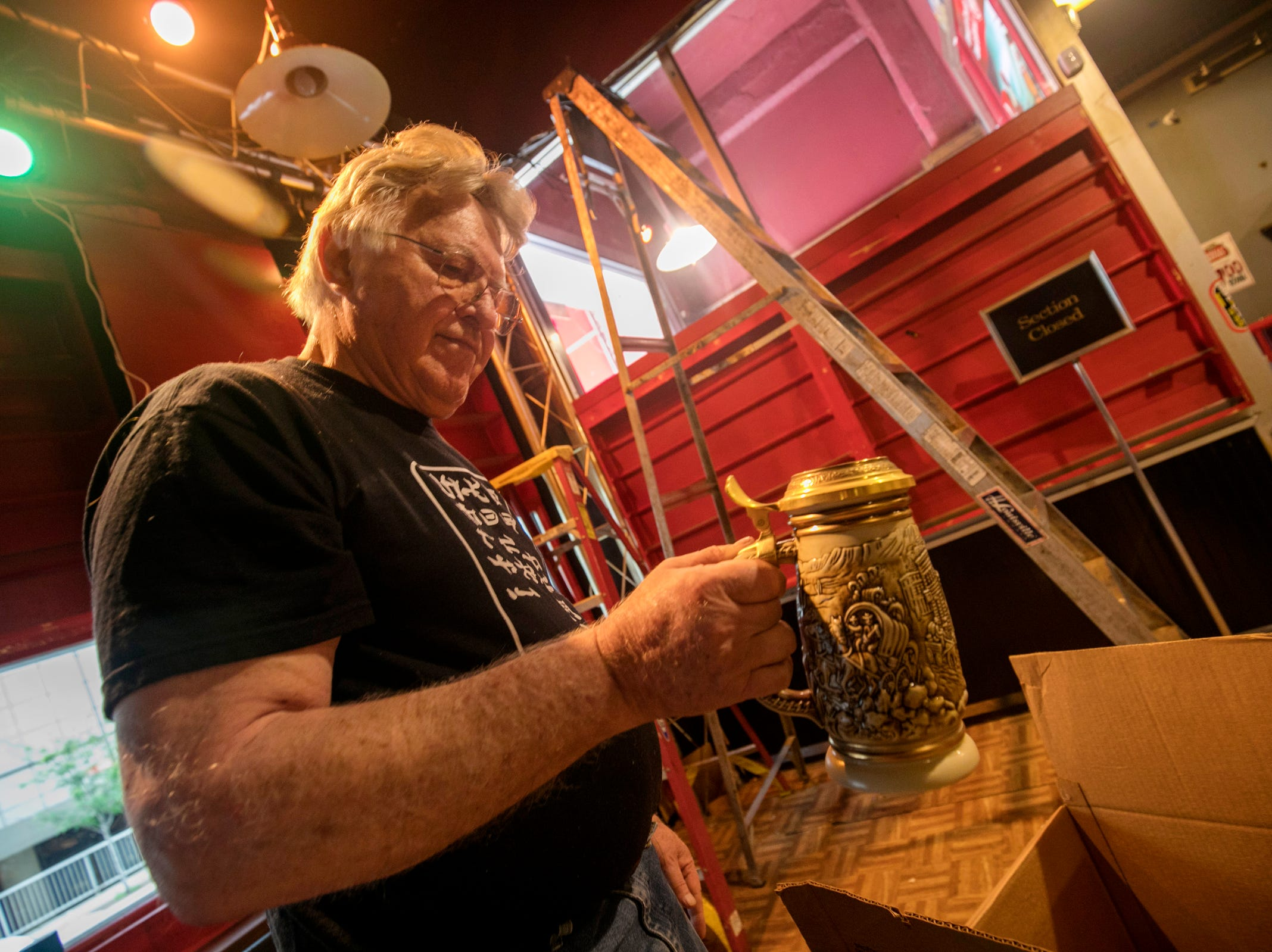 """Cobo Joe's co-owner Richard Cadreau, 71, packs up memorabilia before closing the doors to the sports bar on Tuesday, July 31, 2018. """"It doesn't take much to make people happy,"""" Cadreau said about interacting with customers over the years. """"I have made a lot of friends here,"""" he added."""