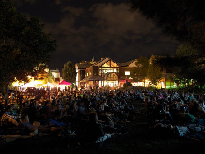 A crowd gathers on New Belgium Brewing's lawn for a bike-in movie.
