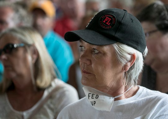 """Bobbi Knight of Cape Coral listens from the front row of the public meeting with the U.S. Army Corps of Engineers on Tuesday. She wore a mask around her neck that read """"Fed Up."""""""