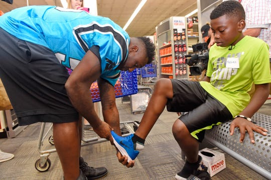 Carolina Panthers' Thomas Davis helps 10-year-old Messiah Robinson shop for shoes at Academy Sports + Outdoors, Tuesday, July 31, 2018, during a back-to-school shopping spree. The NFL player and sports store sponsored the event for 25 local kids.