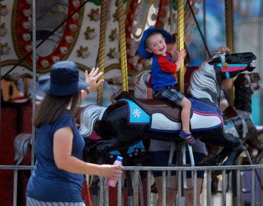 Gibson Seipert smiles to his mom Nicole while riding the merry-go-round at the Mighty Thomas Carnival midway on Tuesday at the Montana State Fair.