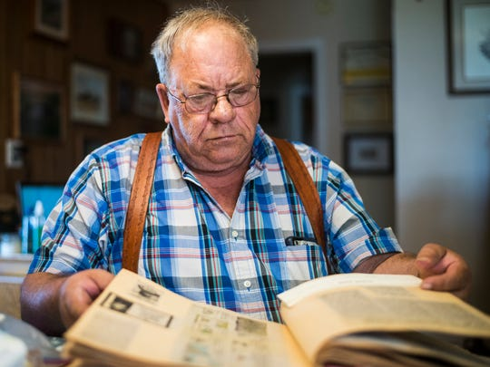 Bob Snodgrass looks through scrapbooks documenting his family's history.