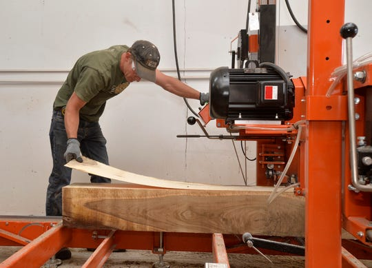 Chris Crocker of The Good Wood Guys uses a sawmill to make an ultra-thin plank during a sawmill demonstration.