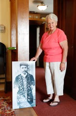 "Peg Brettin, board member and chairman of the accessions for the Starke County Historical Society in Knox Ind. stands next to a life-size photo of Knox's most famous and sometimes forgotten resident, Che-Mah the ""Chinese Dwarf"", the smallest man in the world on Tuesday, July 24, 2018. Che-Mah, 1838-1926, who retired to Knox Ind. from his successful career touring internationally as the smallest man in the world, measured 28 inches tall and weighed 40 pounds."