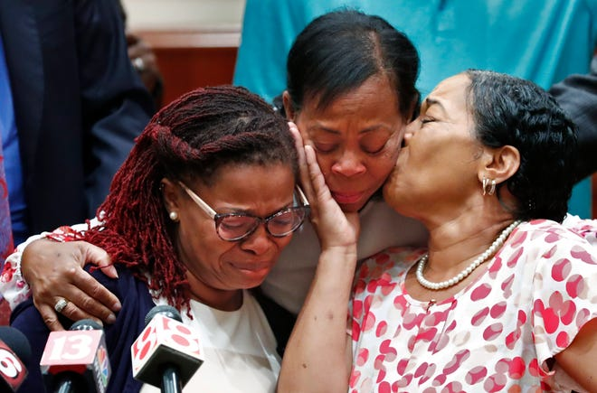 Coleman family and friends hug Kyrie Rose, left, and Lisa Rose Berry, right, after a news conference in Indianapolis to announce a lawsuit on behalf of two victims in the Branson, Missouri, duck boat disaster. Nine members of the Coleman family died.
