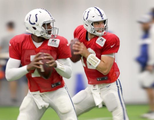 Indianapolis Colts quarterback Andrew Luck (12) and Jacoby Brissett (7) works on passing drills during their fifth day of training camp at Grand Park in Westfield on Tuesday, July 31, 2018.