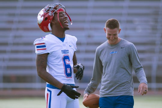 Forest High School outside linebacker Diwun Black (left) jokes around with head football coach Jonathan Worrell (right) after a summer practice.