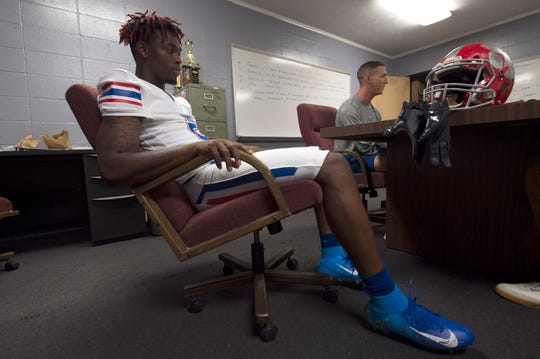 Outside linebacker Diwun Black of Forest High School sits aside head football coach, Jonathan Worrell, during an interview with the Clarion Ledger.