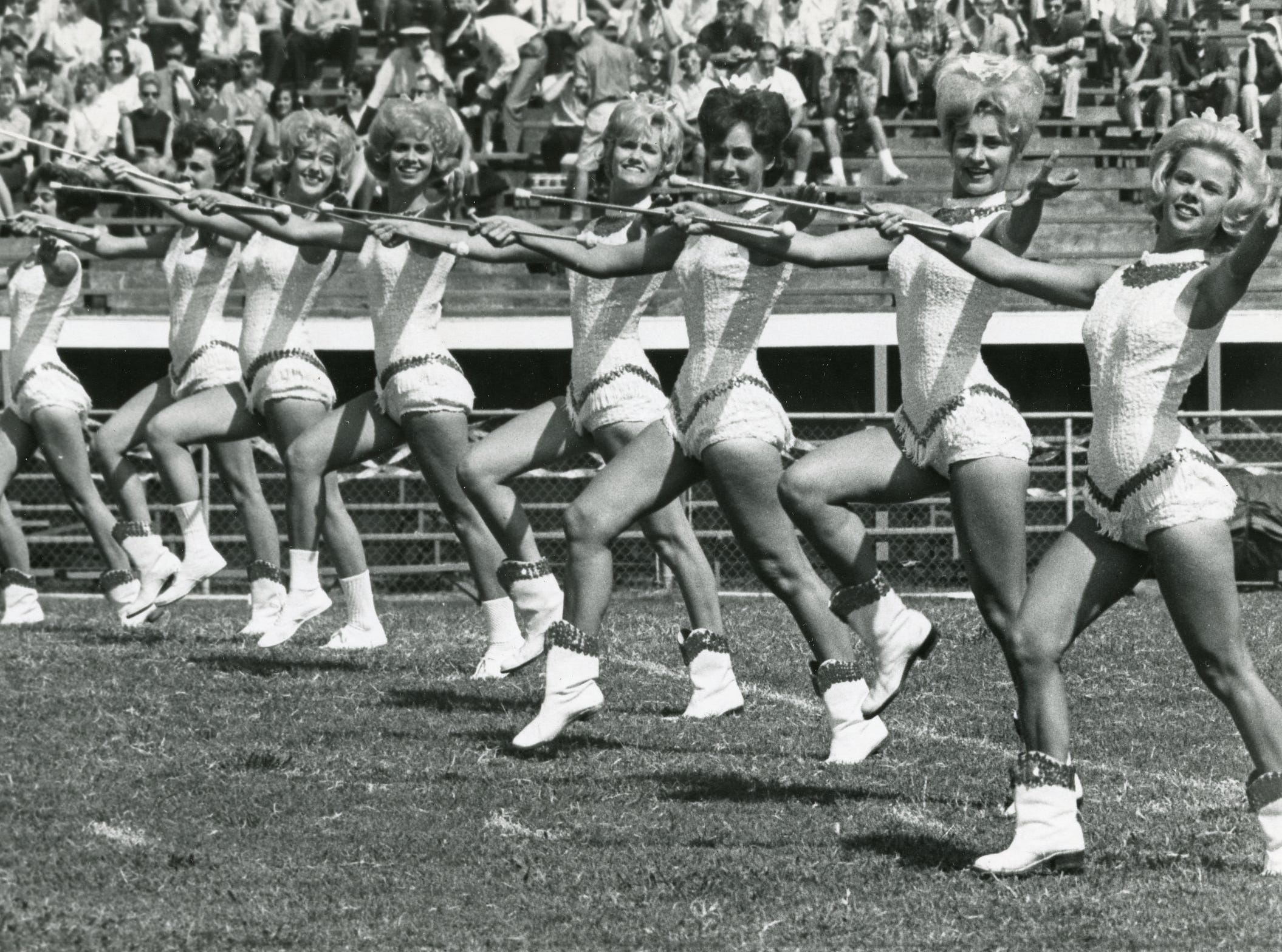 The 1963 UT majorettes perform on the field with the band.