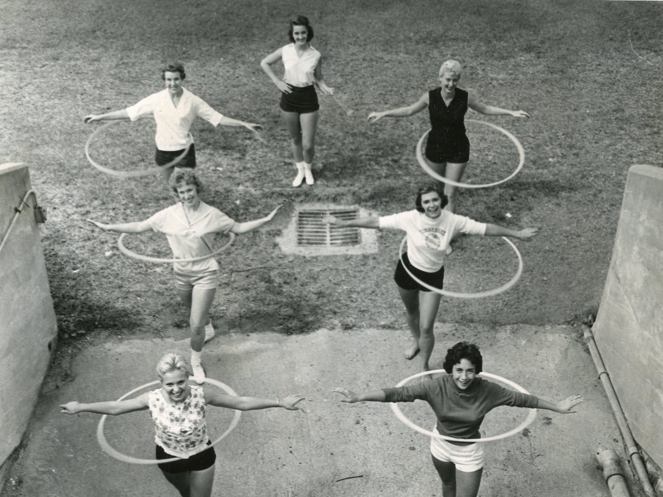 UT majorettes practice a routine using hula hoops in September, 1958. Pictured are Myrna Manning, Brenda Smith, Helen Newport, Celia Wright, Pat Price, Pat Cornett and Claudette Riley (center back). Riley became the first scholarship majorette in the history of the University of Tennessee, and since then she has traversed the nation to teach young girls her art. The first time she did her baton-twirling act at Tennessee in 1958, the other majorettes went through a hula-hoop act.