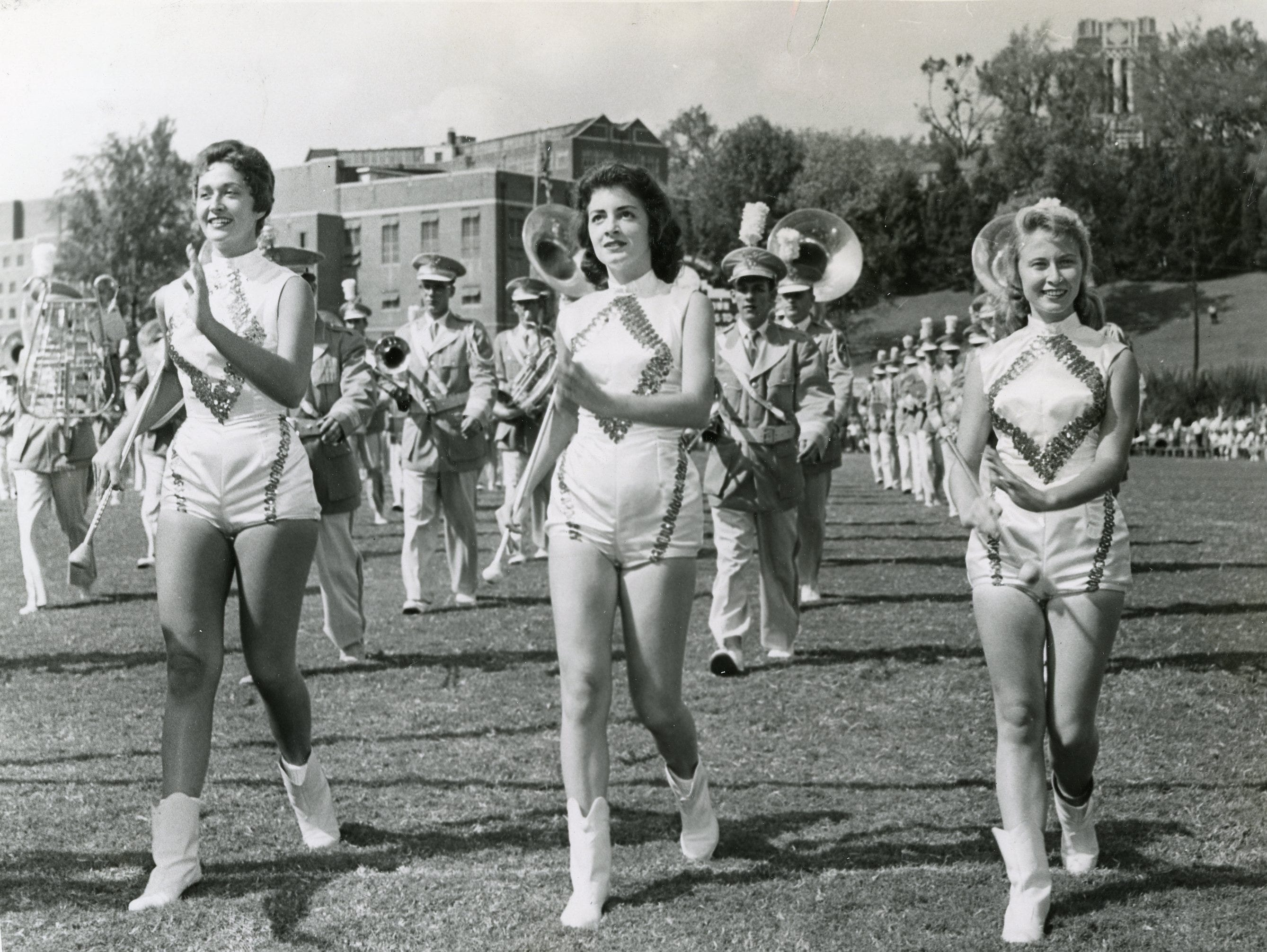 """Phyllis Swann, Celia Wright and Jo Hawk march with the UT band, the 1959-1960 """"Vol Strutters""""."""