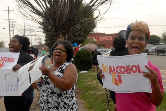 Shawnnika Queen, left, Christina Robinson, center, and Nachand Trabue, right, hold signs in protest at the Family Dollar in the Russell neighborhood. Residents and supporters are trying to prevent the store from selling alcohol.  July 30, 2018