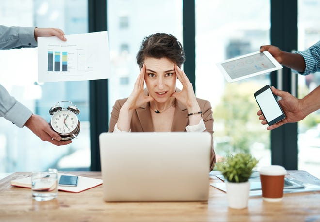 Shot of a young businesswoman looking stressed out in a demanding office environment