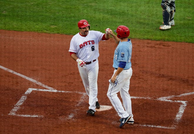 Former Louisville Bats Corky Miller is congratulated at the plate by Mark Teahan after smashing a two-run homer.