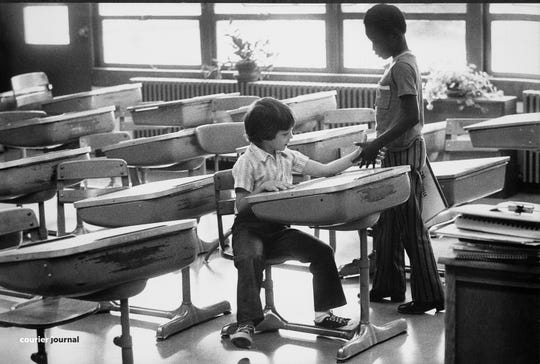 At Greenwood Elementary, Mark Stewart, 8, seated, exchanged introductions with a new classmate, Darrel Hughes, also 8. Sept. 3, 1975