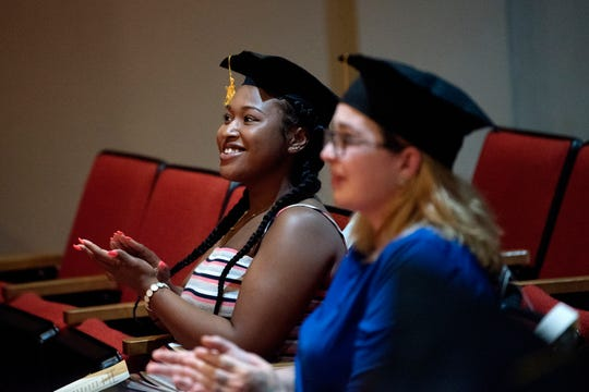 Graduate Tamara Outlaw, left, and Caitlin Merz, clap during the Capital Area Literacy Coalition's GED graduation ceremony on Wednesday, July 25, 2018, at the downtown branch of the Capital Area District Libraries in Lansing.  Some of the grads wore felt caps made for preschoolers. The coalition is hoping to find real caps for future graduations.