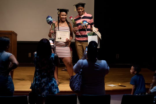 Graduates Tamara Outlaw, left, and her friend Brooklyn Alexander pose for pictures after the Capital Area Literacy Coalition's GED graduation ceremony on Wednesday, July 25, 2018, at the downtown brach of the Capital Area District Libraries in Lansing.