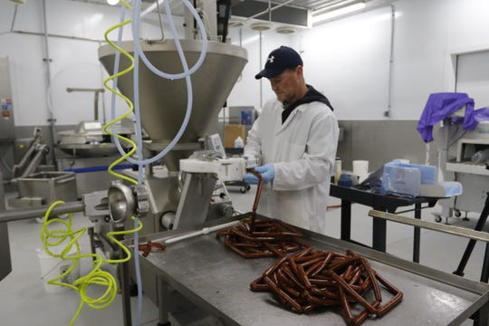 Hewitt's Meat Production Manager Drew Young makes snack sticks in the processing area at the new location of Hewitt's Meat, 210 Downwind Drive Marshfield, Tuesday, July 31, 2018.