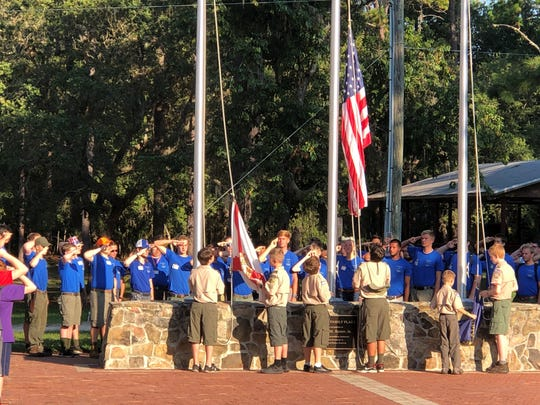 James Olsen, second from left, and Joey Puell, third from right, raise the camp flag with other Florida scouts.