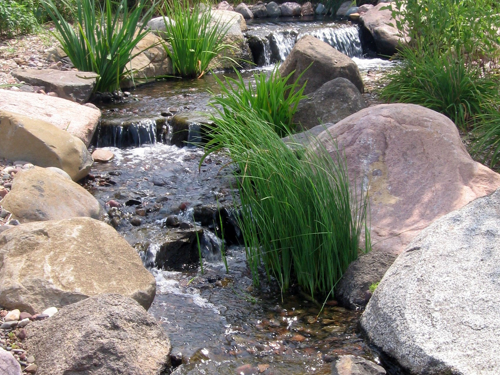 This picture shows a stream with waterfalls built out of granite boulders that flows into a pondless basin. The stream is about 20 feet long and 2 ½ feet wide.