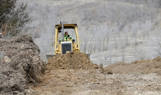 A bulldozer operator with Lei LLC of West Bend moves clean fill at Scenic Pit  on Scenic Road in Richfield in April.