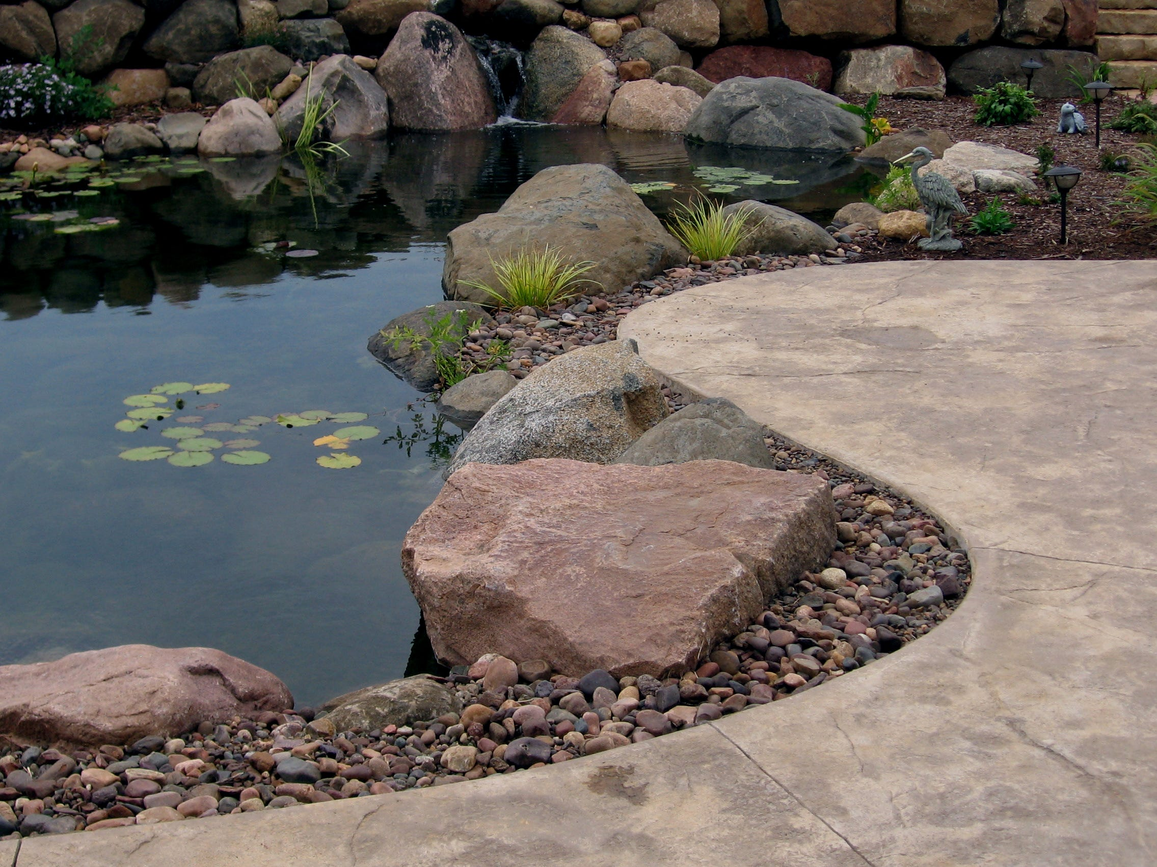 This typical pond edge uses different sizes of boulders to create a natural look. It's built right up to the edge of the patio, which allows interacting with and viewing of a water feature. A large seat stone invites homeowners to sit and dangle their feet in the water.