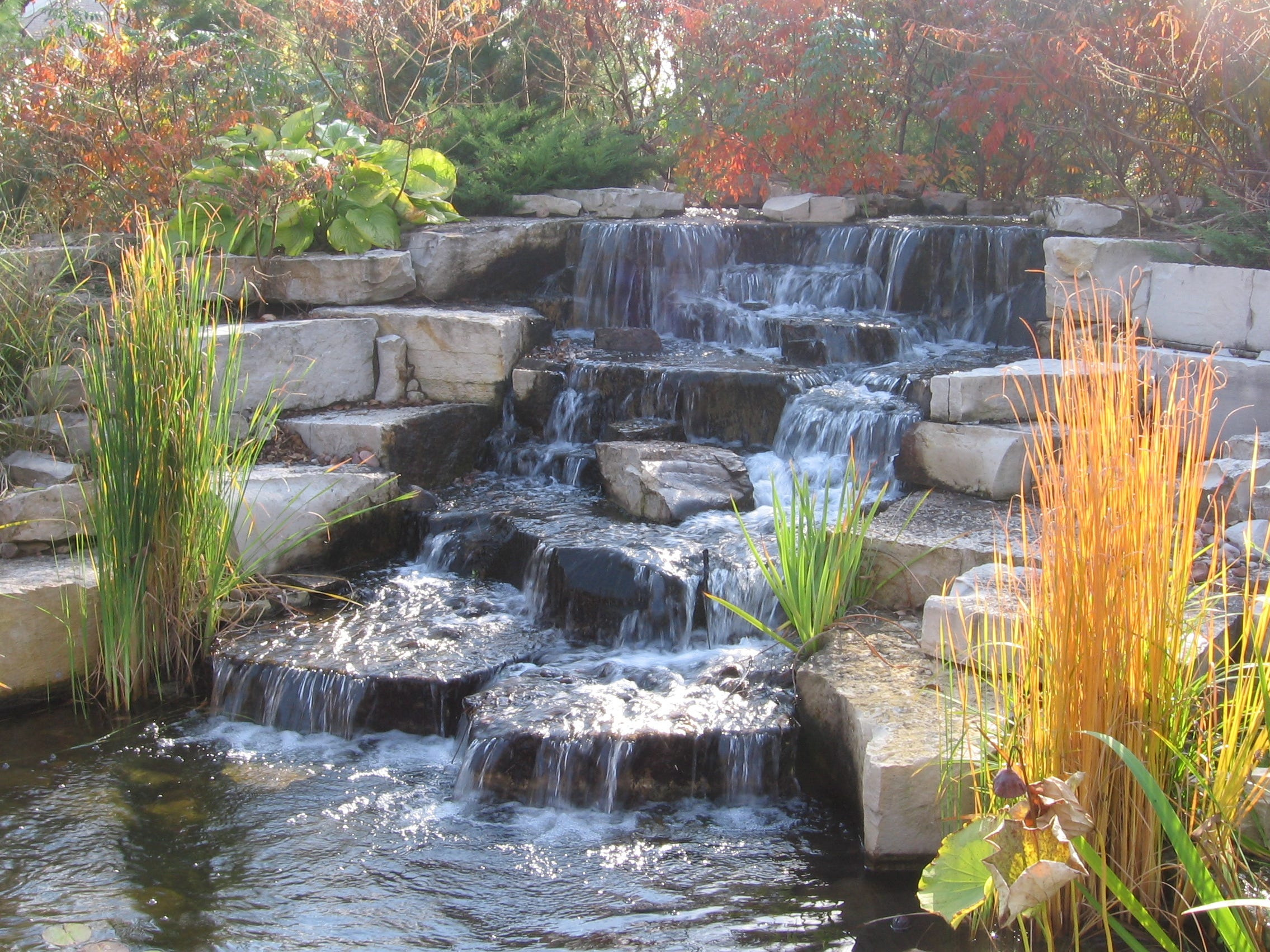 This waterfall has a grade change of about 5 feet and has waterfalls that are about 6 feet wide and flow into a 15-by-30-foot pond. The water feature was built using Lannon stone.