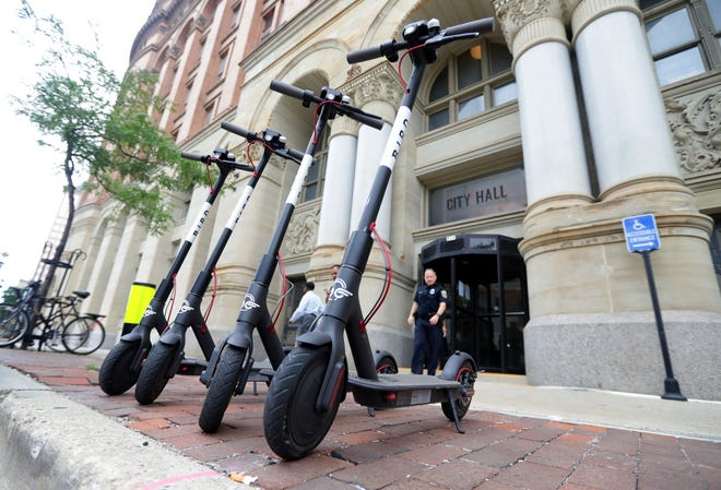 Bird scooters are lined up for use outside Milwaukee City Hall.