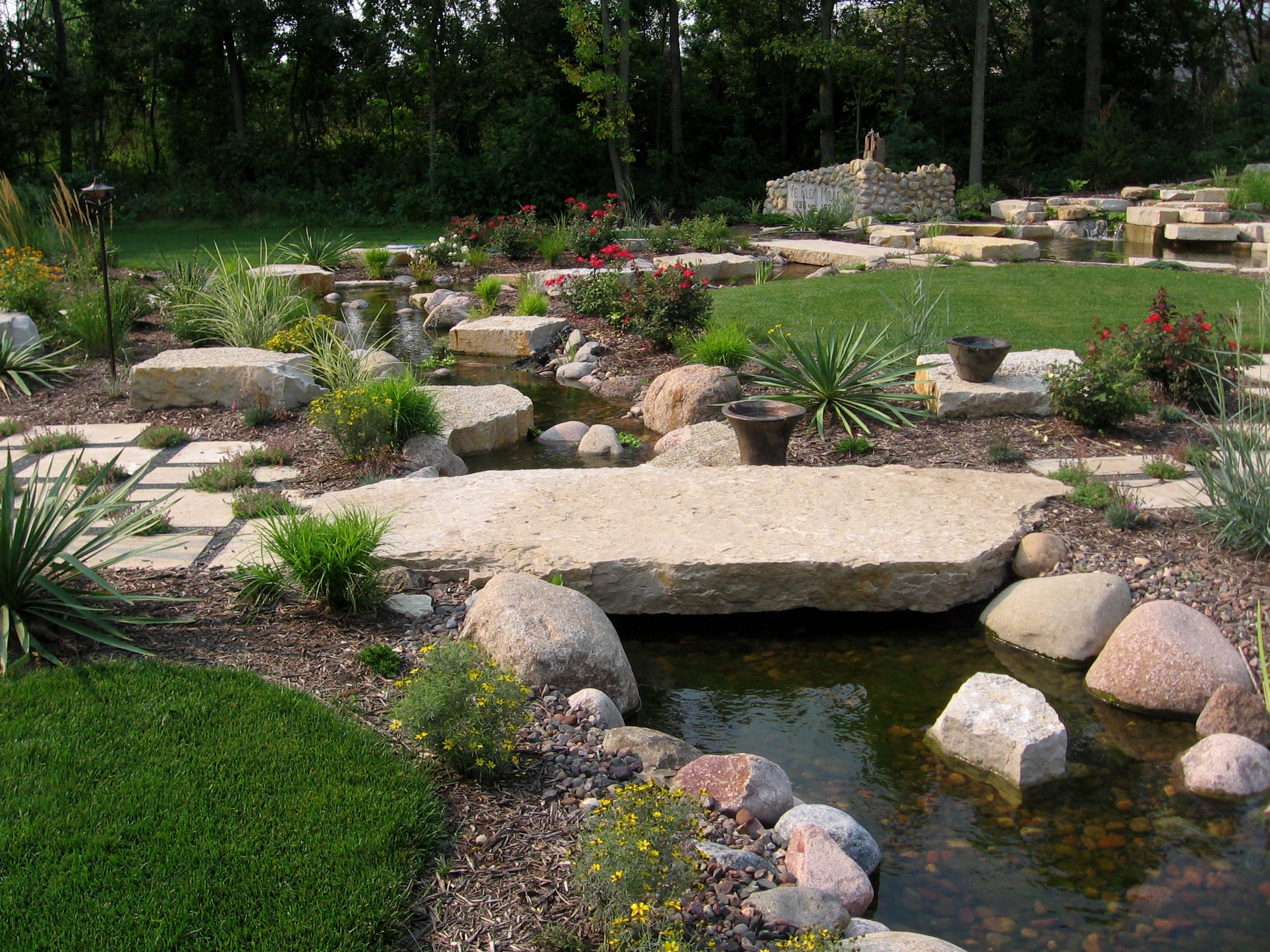 This 195-foot-long stream meanders through a backyard and flows into some woods, giving the illusion that the stream continues on for a distance. It is built out of granite boulders with Lannon stone accents and features a large stone bridge that the homeowners can cross over to get to a patio with a fire pit.