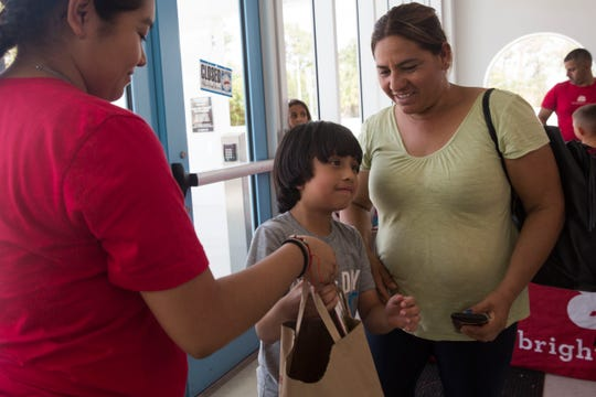 Victoria Salas, left, hands a grocery bag full of healthy produce to Albeiro Juarez and his mother, Gregonia Franco, during the Brighter Bites program hosted at the Boys & Girls Club of Collier County on Wednesday, July 25, 2018.