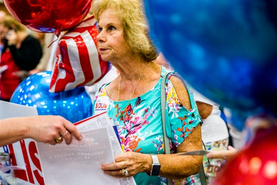 Hedy Weinberger, of Naples, gathers information about candidates during Politics in the Park at the Naples Area Board of Realtors in Naples on Tuesday, July 31, 2018. Attendees met with local and state candidates up for commissioner seats, school board seats, fire district, and state Senate and representative seats.