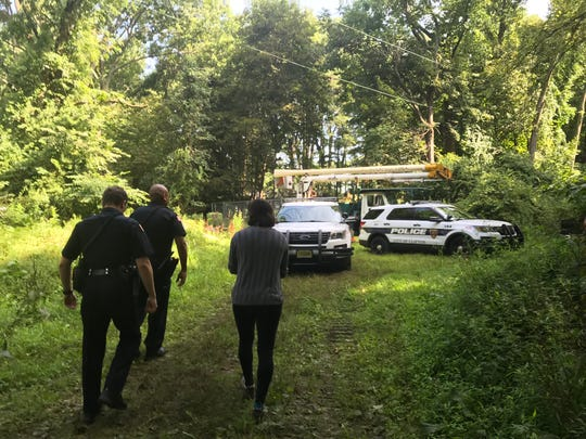 Clifton Police escort Madeline Grupper, 25, of Montclair, out of the Bonsal Preserve on Tuesday morning, July 31, 2018.