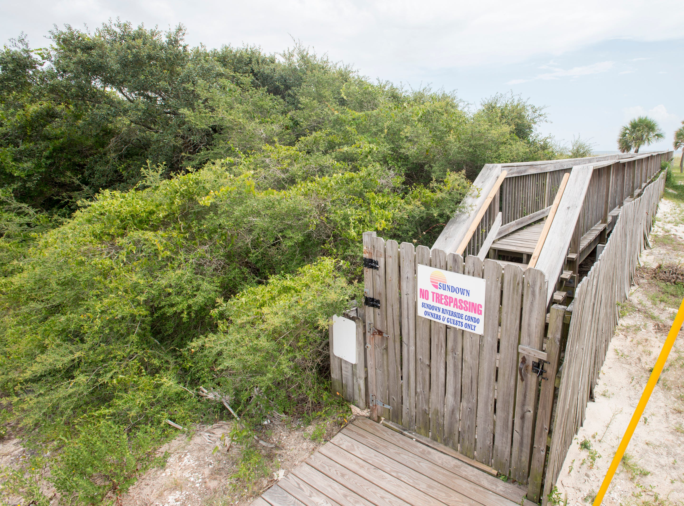 A private walkover owned by Sundown Riverside Condos runs in between the Crab Trap restaurant and beachfront property owned by Escambia County in Perdido Key.   Tuesday, July 31, 2018.  The county owned property currently sits vacant with no public parking and no public access to the beach.