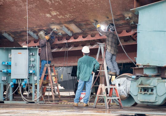 Welders work on the hull of a 121-foot midwater trawling ship at the Patti Shipyard in Pensacola on Tuesday.