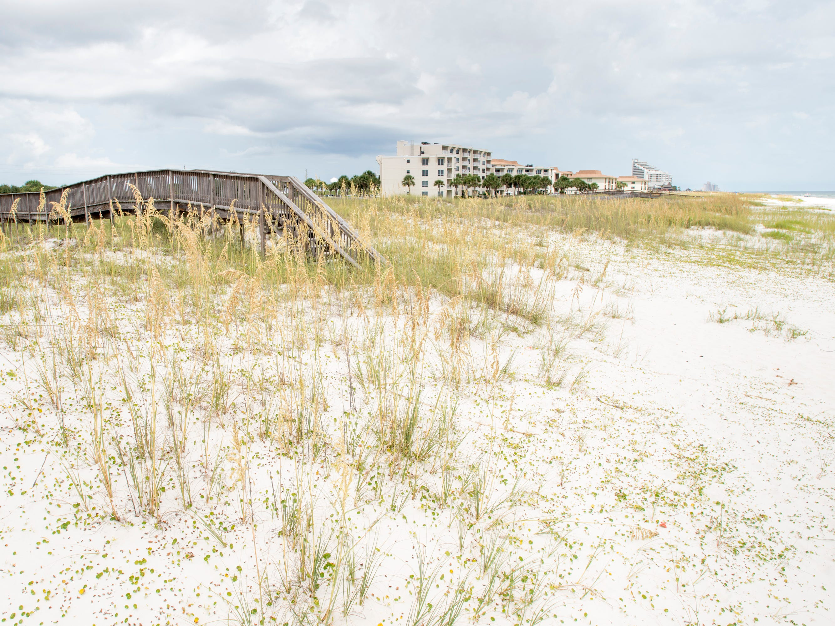 A private walkover owned by Sundown Riverside Condos runs in between the Crab Trap restaurant, to the left, and beachfront property owned by Escambia County in Perdido Key.   Tuesday, July 31, 2018.  The county owned property currently sits vacant with no public parking and no public access to the beach.
