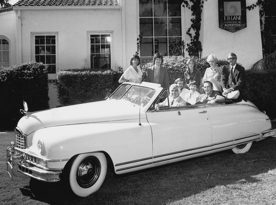 E. B. Lane founder Ed Lane, along with his staff, poses behind the wheel of Lane's 1948 Packard. The 1975 photo shows them in front of the firm's historic offices on McDowell.