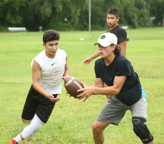 Joey Furlong hands off to AlexAlcera during a football workout session at Pawling High School on July 30, 2018.