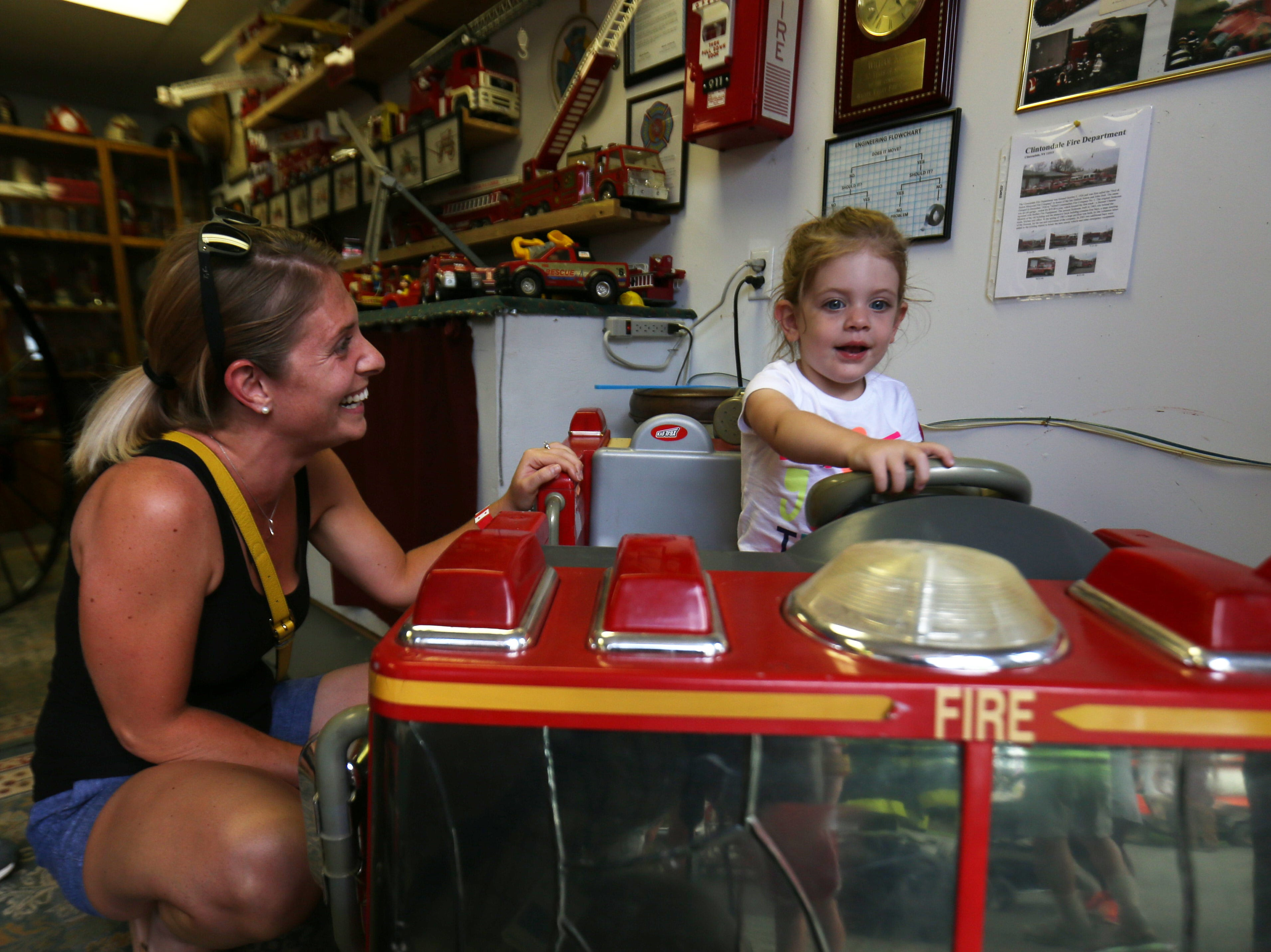 Amanda Albert of Newburgh watches her daughter, Lily, play on a toy fire truck in the fire department museum at the Ulster County Fair in New Paltz on July 31, 2018.