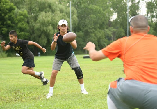 Assistant coach, Billy Rodriguez snaps the ball to Joey Furlong as Ruben Velazquez moves into position to receive the handoff during a football workout session at Pawling High School on July 30, 2018.
