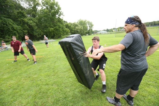 Assistant coach, Joe Giannantonio instructs  Jacob McMahon during a football workout session at Pawling High School on July 30, 2018. Pawling is switching to an 8 man format for the 2018 football season.