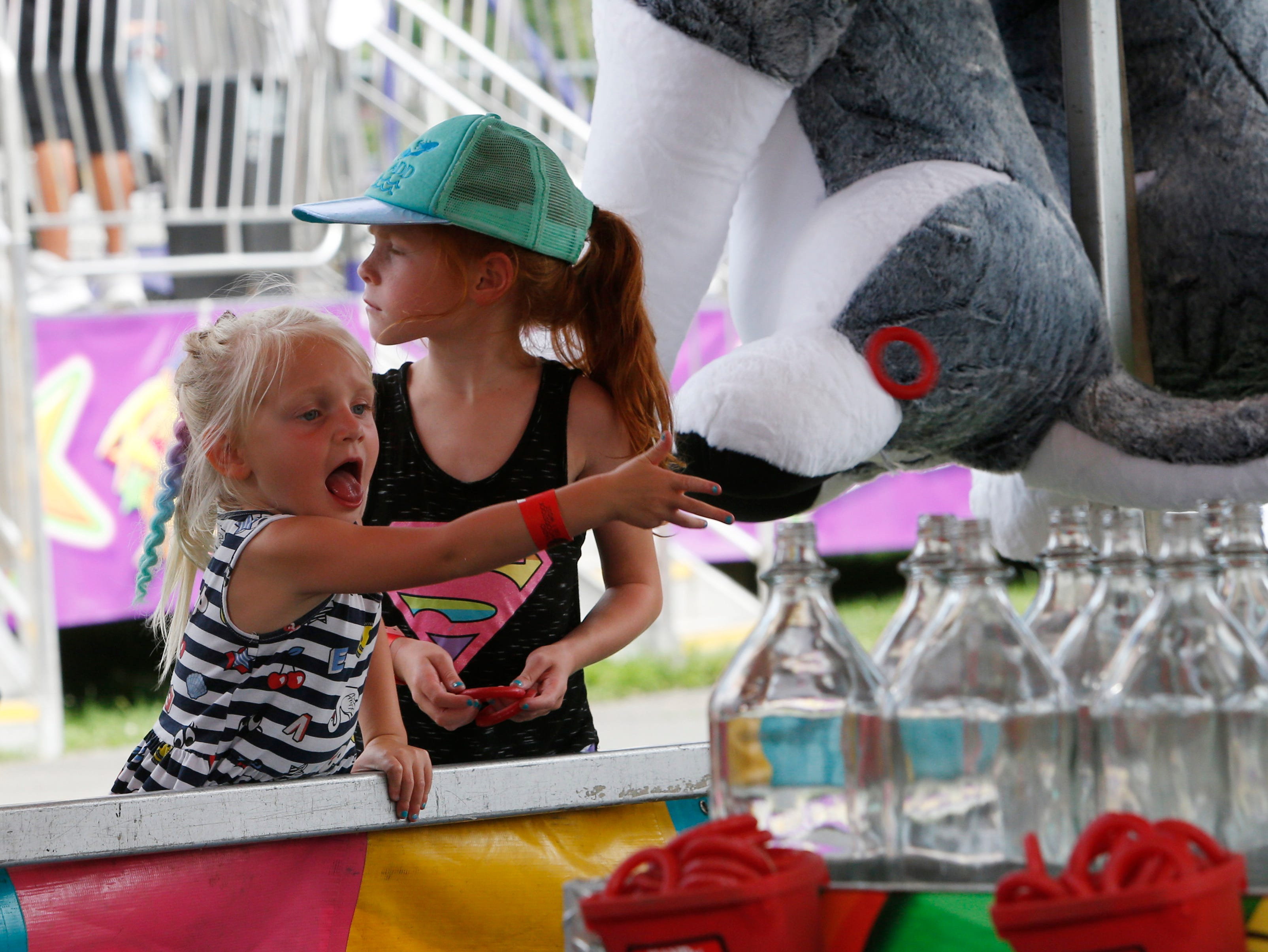 From left, Harper and Addison Fabiano of Kingston try their luck at the ring toss during the Ulster County Fair in New Paltz on July 31, 2018.