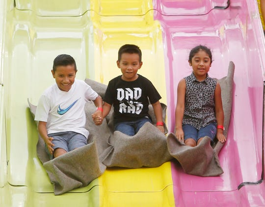 From left, Yoel Cruz, Alexander Francisco and Meyali Martinez of Poughkeepsie enjoy a trip down the slide at the Ulster County Fair in New Paltz on July 31, 2018.