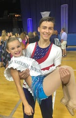 Pawling's Robert Leske lifts 9-year-old Madison Anderson of Hopewell Junction after both won national baton twirling titles in Indiana last weekend.