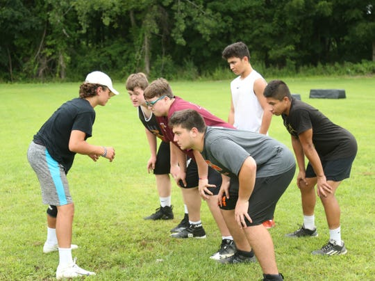 Joey Furlong gives leads the huddle during a football workout session at Pawling High School on July 30, 2018.