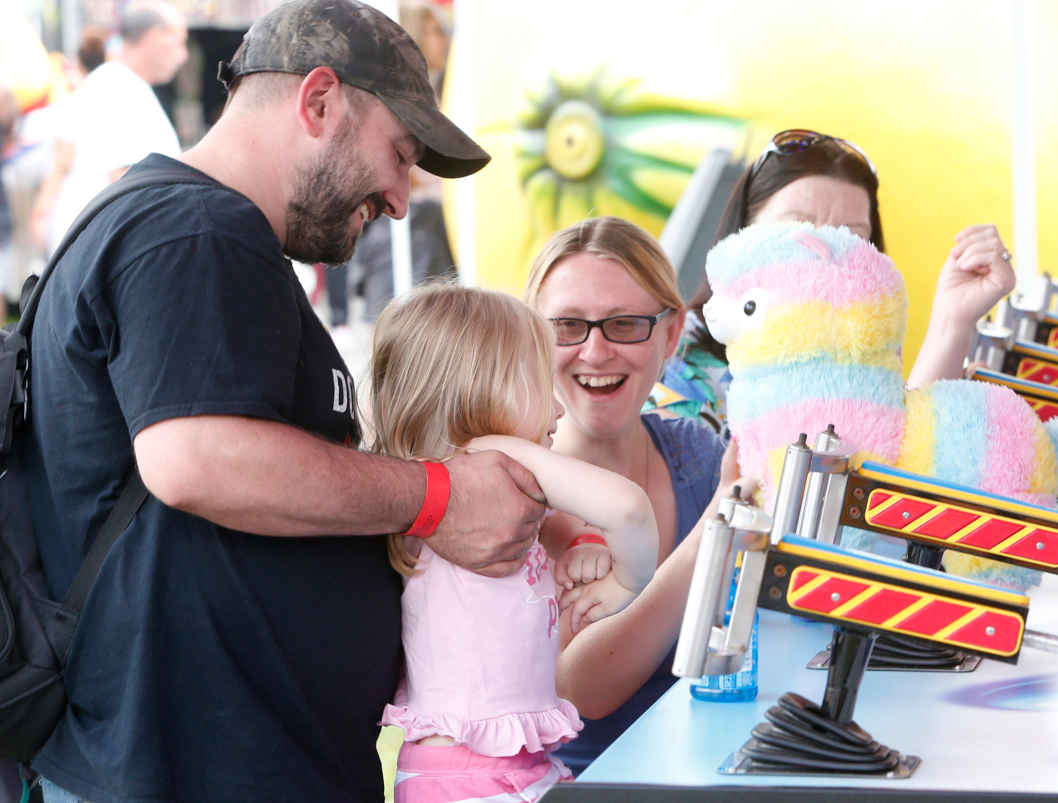 Chaz Coddington holds his daughter, Alana, as wife, Faith, cheers her for winning a prize during the opening day at the Ulster County Fair in New Paltz on July 31, 2018.