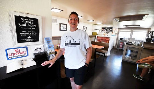 Melanie Schmuck, one of the owners, stands in the ice cream parlor that was once a pull-through garage in the Haines Shoe House.
